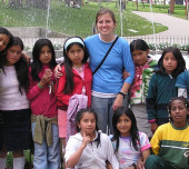 Volunteer with students in front of fountain in Ecuador