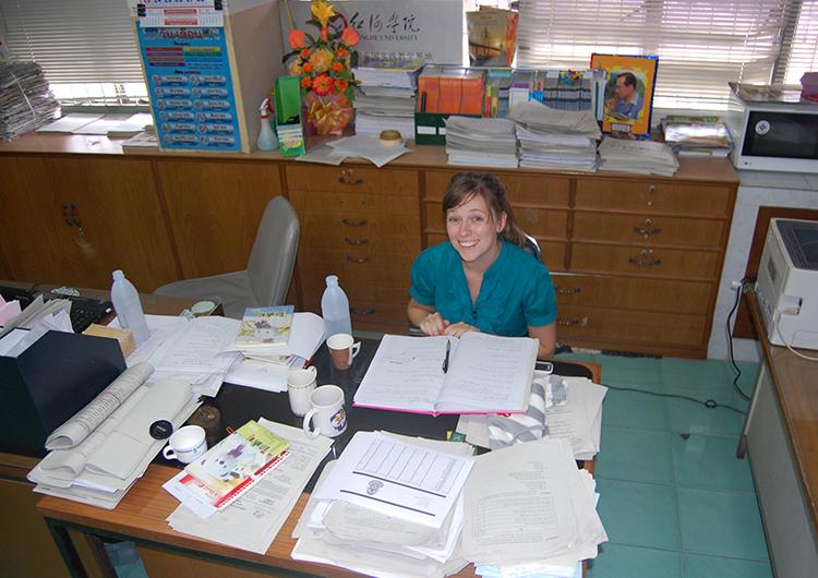 An English teacher at a desk in Thailand.