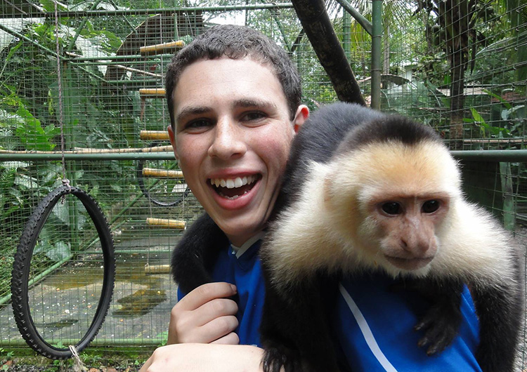 A Greenheart Travel volunteer in Costa Rica holding a monkey.