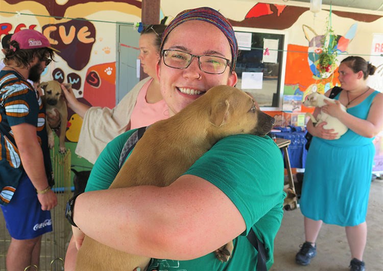 A Greenheart Travel volunteer holds a puppy in Thailand.