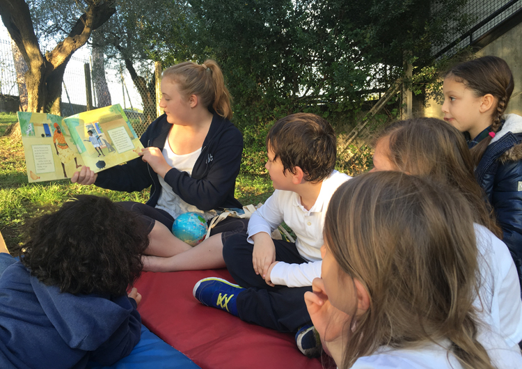 Some students and a teacher reading together outdoors.