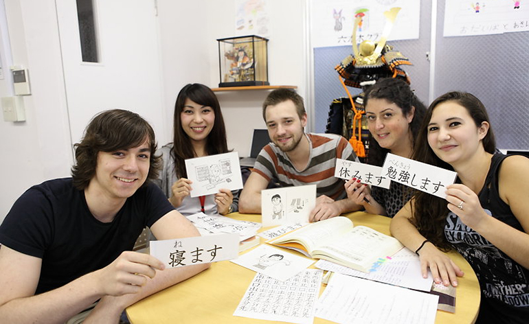 A group of students hold up Japanese writing.