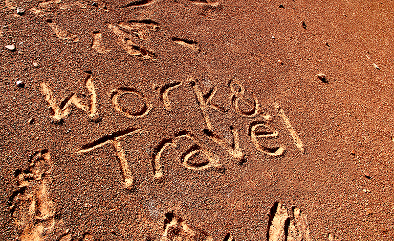 The words work and travel sketched on a beach in Australia.