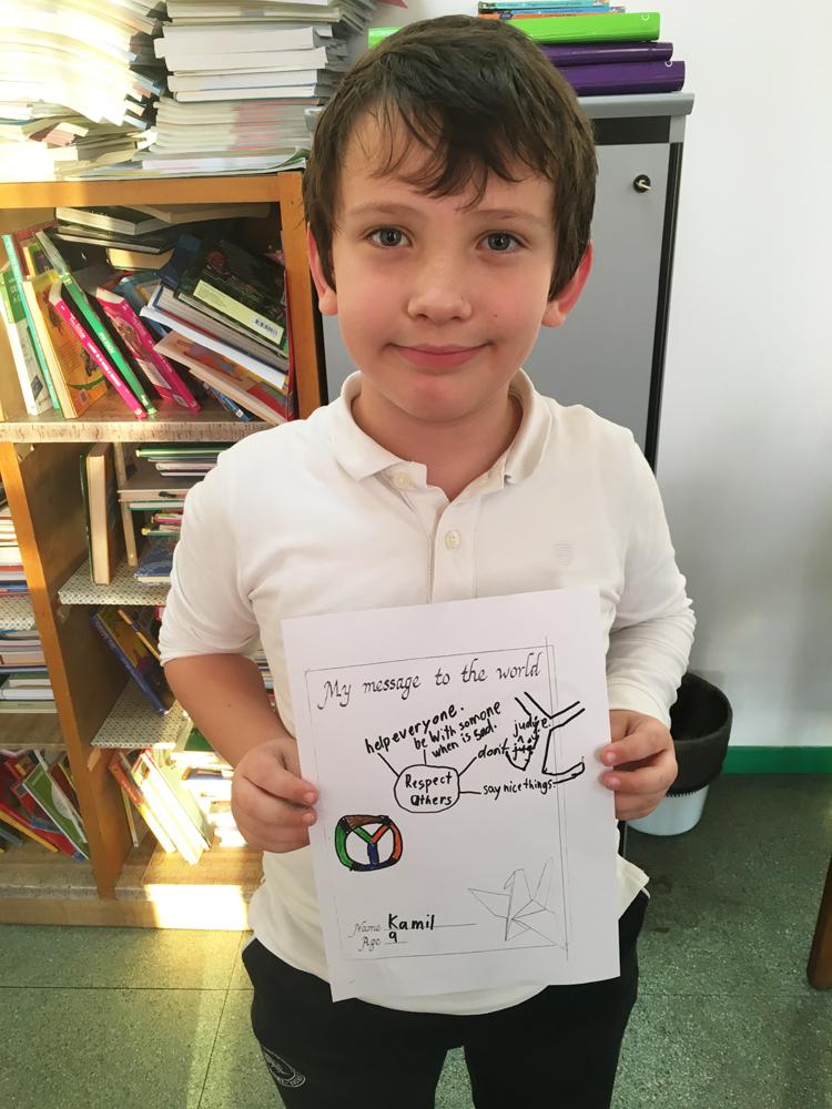 A boy shows his artwork.