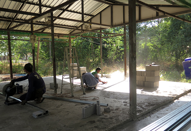 Workers constructing a new dog kennel in Thailand.