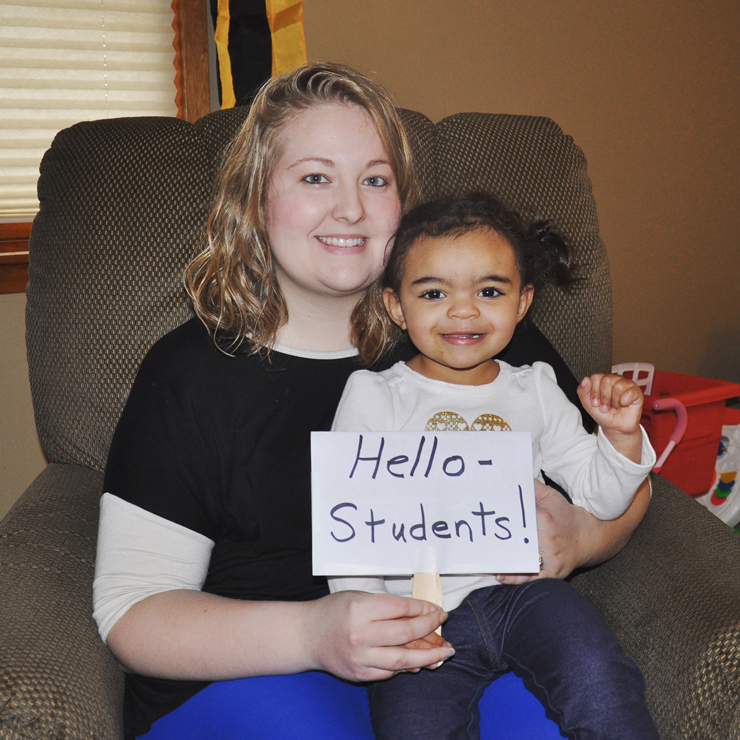 A teacher abroad's sister and niece greetings his students.