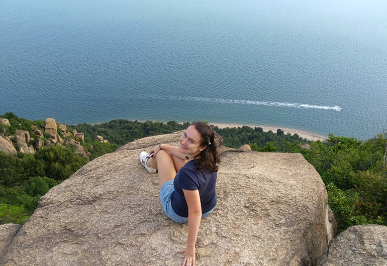 Greenheart Traveler, Maggie, on a cliff overlooking the ocean off the coast of Japan.