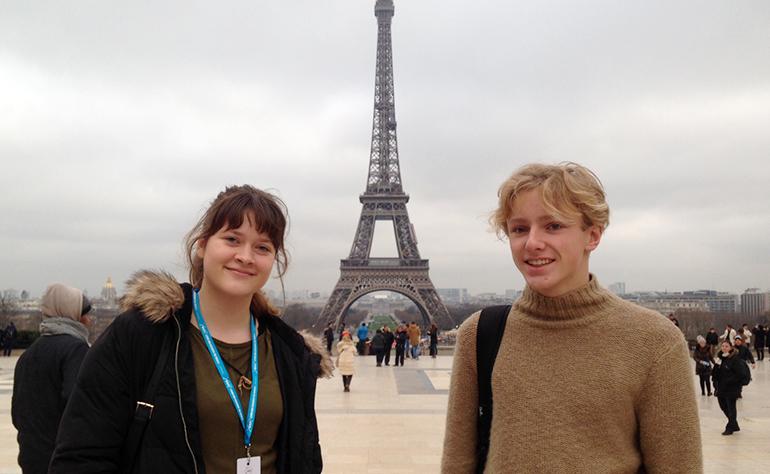Greenheart Traveler, Ian Taraszewski, with a friend in front of the Eiffel Tower in Paris, France.