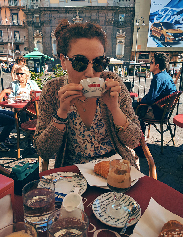 Mikaela drinking espresso and having a cornetto at a cafe in Naples, Italy.