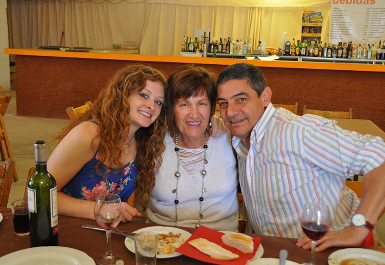 A student has dinner with her homestay parents in Spain.