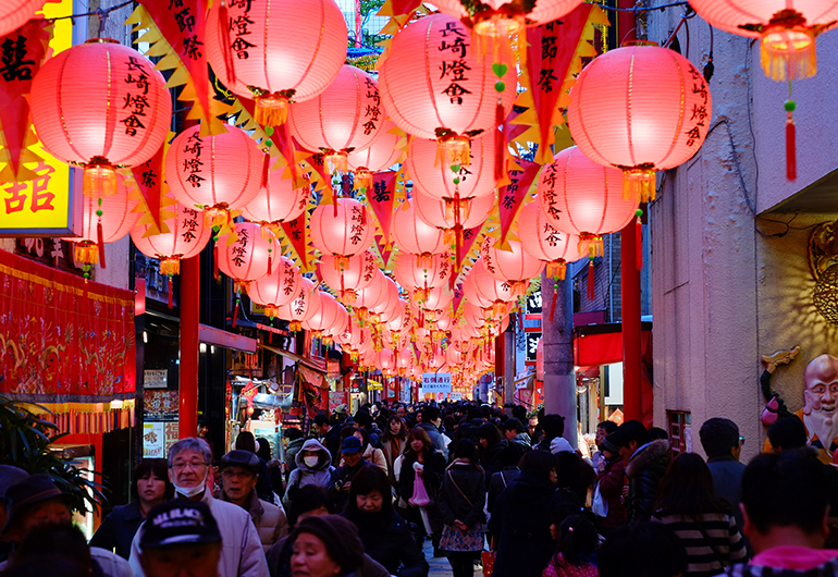 A latern festival lining the street in Japan at night.