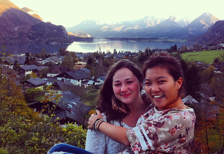 Two study abroad students hugging each other in Salzburg, Austria with mountains in the background.