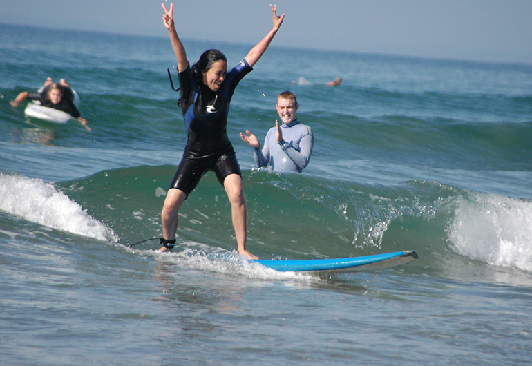 Student triumphantly riding a wave in Australia.