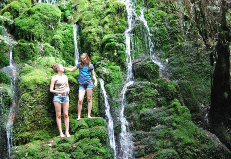 Two students climbing the waterfalls in New Zealand.