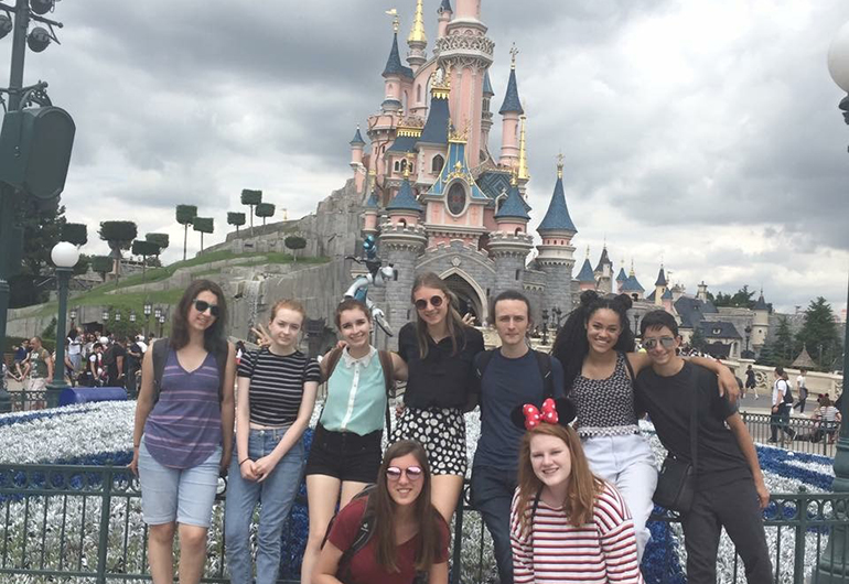 Noam and her new friends posing in front of the castle at Disneyland Paris.