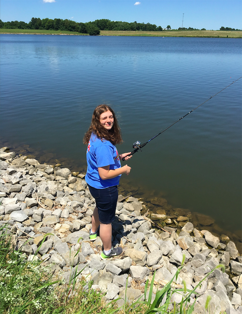 Emily fishing on the rocks at a family reunion.