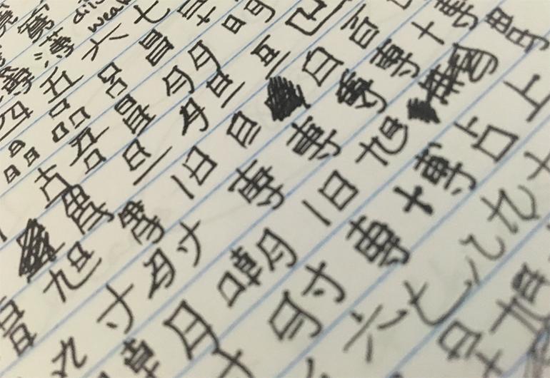 Emily's notebook with Japanese kanji writing.